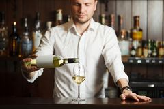 Sommelier in shirt pouring white wine into glass. Placed on broad bar counter, man wine steward filling wineware with dine beverage alcoholic drink, rows of royalty free stock photos