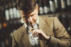 Sommelier som luktar anstrykning av whisky i bokal på bakgrund av hyllor med flaskor i källare arkivfoto