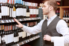 Sommelier in the store near shelves. Store audit. Young handsome salesman in a liquor store examining rows of wine bottles Royalty Free Stock Photo