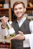 Sommelier in the store near shelves. Confident sommelier. Close-up of a handsome young sommelier holding a wine bottle and stretching it out to the camera Stock Image