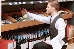 Sommelier in the store near shelves Stock Photography