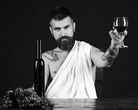 Sommelier tastes drink. Man with beard holds glass of wine on brown background. Winemaking and degustation concept. God Bacchus with smile on face wearing Stock Photos
