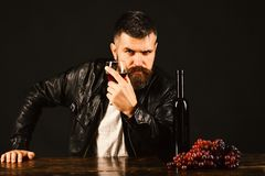 Sommelier tastes expensive drink. Winetasting and degustation concept. Man with beard holds glass of wine on dark brown background. Degustator with strict face Royalty Free Stock Photography