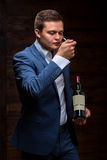Sommelier tasting red wine. Sommelier smells blended whiskey in nosing glass. Caucasian businessman smells a malt whisky in nosing glass. Satisfied mature Royalty Free Stock Photos