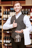 Sommelier with a tray and glasses. This wine is just perfect. Confident male sommelier showing thumbs up and holding wine glasses while standing near the wine Royalty Free Stock Photos