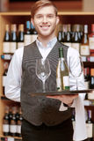 Sommelier with a tray and glasses. You should taste this perfect wine. Handsome young man in waistcoat holding bottle and glasses while standing in liquor store Stock Images