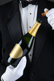 Sommelier Uncorking Champagne Bottle. Closeup of a Sommelier uncorking a champagne bottle. Man is unrecognizable wearing a tuxedo and white gloves. Vertical Royalty Free Stock Photo