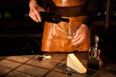Sommelier wearing apron pouring wine into a glass. Cheese and accessories placed on a wooden table. Sommelier wearing apron pouring wine into a glass. Cheese royalty free stock photos
