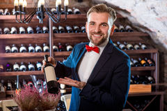 Sommelier in the wine cellar. Sommelier with wine bottle in the wine cellar royalty free stock image