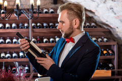Sommelier in the wine cellar. Sommelier with wine bottle in the wine cellar Stock Photography