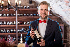 Sommelier in the wine cellar. Sommelier with wine bottle in the wine cellar Stock Photo