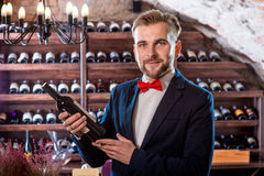Sommelier in the wine cellar. Sommelier with wine bottle in the wine cellar Royalty Free Stock Photos
