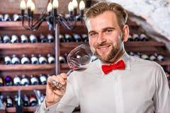 Sommelier in the wine cellar. Sommelier checking wine in the glass in the wine cellar Royalty Free Stock Photo