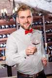 Sommelier in the wine cellar. Sommelier kneading wine in the wine glass in the wine cellar stock photography