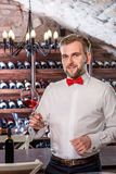Sommelier in the wine cellar. Sommelier kneading wine in the wine glass in the wine cellar Stock Photo