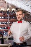 Sommelier in the wine cellar. Sommelier kneading wine in the wine glass in the wine cellar stock photo