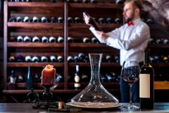 Sommelier in the wine cellar. Sommelier looking for good wine on the storage in the wine cellar stock images
