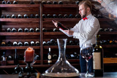 Sommelier in the wine cellar. Sommelier looking for good wine on the storage in the wine cellar Stock Photos