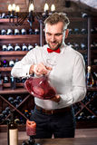 Sommelier in the wine cellar. Sommelier mixing wine in the decanter in the wine cellar Royalty Free Stock Photography