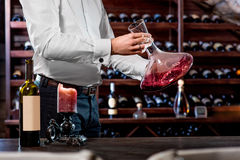 Sommelier in the wine cellar. Sommelier mixing wine in the decanter in the wine cellar Stock Photo