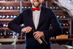 Sommelier in the wine cellar. Sommelier opening wine bottle in the wine cellar royalty free stock photo