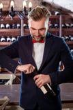 Sommelier in the wine cellar. Sommelier opening wine bottle in the wine cellar Stock Image