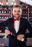 Sommelier in the wine cellar. Sommelier opening wine bottle in the wine cellar royalty free stock image