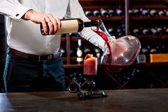 Sommelier in the wine cellar. Sommelier pouring wine to the decanter in the wine cellar Stock Photos