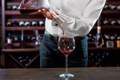 Sommelier in the wine cellar. Sommelier pouring wine to the glass in the wine cellar royalty free stock photography