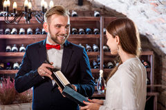 Sommelier in the wine cellar. Sommelier showing wine bootle to women in the wine cellar Stock Image