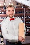 Sommelier in the wine cellar. Sommelier showing wooden wine box with expensive wine in the wine cellar royalty free stock image