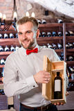 Sommelier in the wine cellar. Sommelier showing wooden wine box with expensive wine in the wine cellar Royalty Free Stock Photos