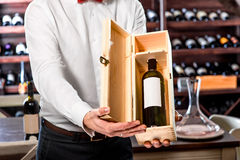 Sommelier in the wine cellar. Sommelier showing wooden wine box with expensive wine in the wine cellar Stock Photo