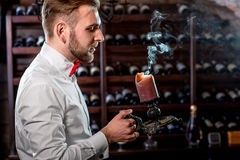 Sommelier in the wine cellar. Sommelier snuffing out candle light with smoke in the wine cellar Stock Photos