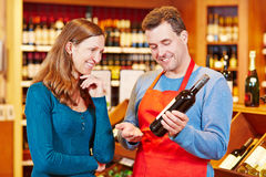 Sommelier in wine store giving. Women recommendation for bottle of wine royalty free stock images