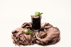 Sommelier and wine tasting concept. Mulled wine in glass. With decor. Glass of red hot wine on white background with brown cloth. Mint leaves, cinnamon, anise royalty free stock photography