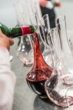Sommelier at work, pouring wine to decanter while standing near the wine shelf. Luxury Diner stock images