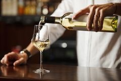 Sommelier working pouring fine alcohol in glass. Sommelier working pouring fine alcohol beverage from bottle with label, white wine in glass for people to drink stock photos