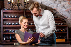 Sommelier with young woman on degustation in the. Sommelier helping young women to choose wine in the cellar. Wine degustation stock photography
