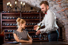 Sommelier with young woman on degustation in the. Sommelier helping young women to choose wine in the cellar. Wine degustation stock images