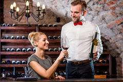 Sommelier with young woman on degustation in the. Sommelier helping young women to choose wine in the cellar. Wine degustation royalty free stock image