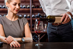 Sommelier with young woman on degustation in the. Sommelier pouring wine to the glass with woman in the cellar. Wine degustation stock images