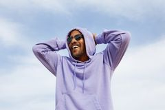 Sommer Active trägt Konzept zur Schau Lächelnder glücklicher junger afro-amerikanischer Mannhippie im Sportkapuzenpulli und Sonne Stockbild