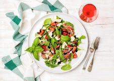 Sommer Arugula, Prosciutto, Erdbeersalat mit Glas rosafarbenem Wein Lizenzfreies Stockfoto