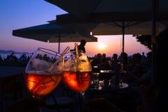 Sommer, der orange Cocktail in einer Bar durch das Meer bei dem Sonnenuntergang glättet Stockbild