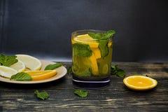 Sommer, erneuerndes Orangensaftgetr?nk mit den tadellosen und orange Scheiben Dunkler h?lzerner Hintergrund Weicher Fokus stockfoto