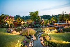Sommer evening in beautiful flowering garden with pond and little creek. royalty free stock photos