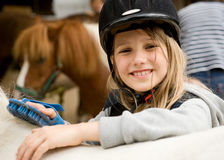 Sommer at farm. Little girl cleaning the horse with brush Royalty Free Stock Photos