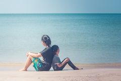 Sommer-Ferien und Feiertags-Konzept: Glückliche Familientagesreise in dem Meer, die Frau und Kind, die zurück zu Rückseite sitzen stockbild