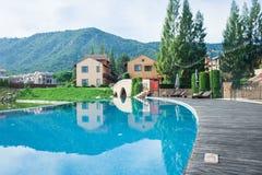 Sommer-Ferien und Feiertags-Konzept: Hölzerne Bahn oder Fußweg neben Swimmingpool mit schöner Landschaftsansicht lizenzfreie stockfotos